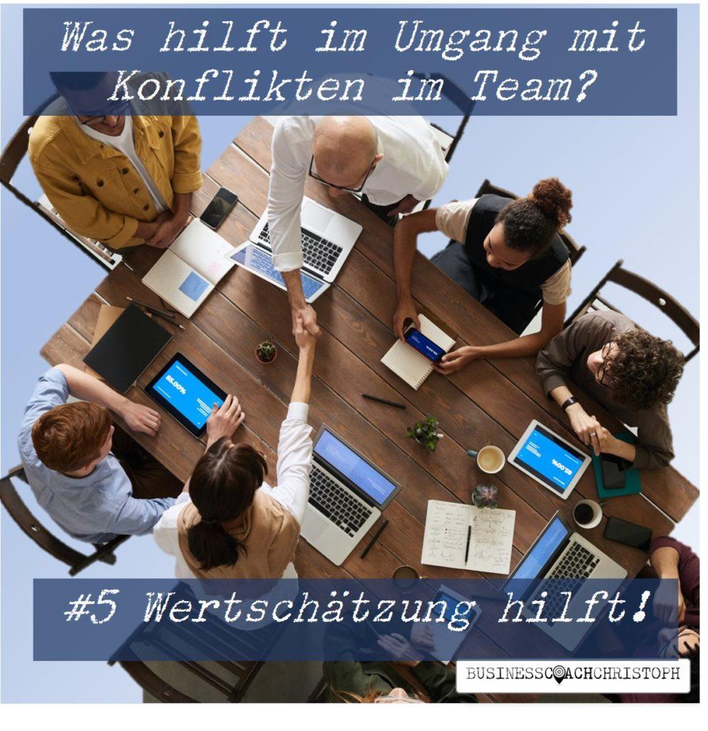 Mehrere Kollegen sitzen am Tischen und zwei geben sich die Hand